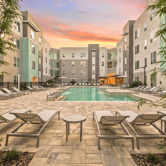 The Tiffany at Maitland West Apartments, exterior, sparkling blue pool, lounge chairs, apartment pool deck courtyard